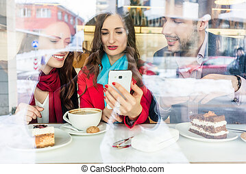 Fashionable young woman showing to her best friends pictures on the mobile