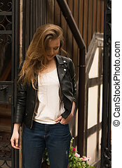 Fashionable young woman with long hair wearing leather jacket, posing at the street
