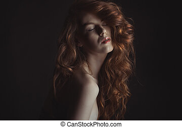Fashionable young woman with shiny hair in the dark