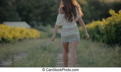Fashionably dressed girl in a short skirt walks along the vineyard