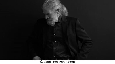 Fashioned old man in tux standing in a studio on black background, looking to the camera, shares, stock, money. Black and white. Prores 422
