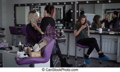 Fashionistas spend their free time in a beauty salon. A girl with dyed hair, talking on the phone while working make-up artist. Blonde girl waits when her stylist finish making her beautiful hairdo.