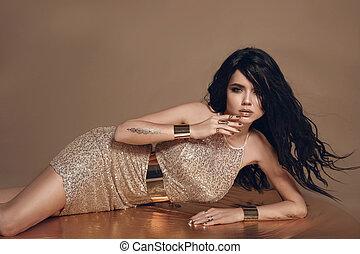 fason, fotografia, od, piękny, sexy, brunetka, kobieta, z, długi, podmuchowy, włosy, i, złoty, jewelry., samica, w, luksusowy, blask, strój, leżący, na, beżowy, studio, tło.