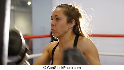 Fast and hard hitting female boxer training in boxing club -...