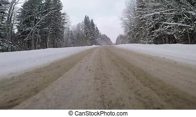 fast driving in a car on a country road in winter. back view