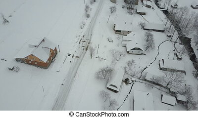Fast flight over a car moving on winter road in Carpathian village. Bird's eye view of snow-covered houses. Rural landscape in winter.