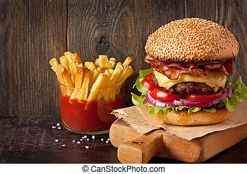 Fast food. - Big delicious cheeseburger stacked high with a ...