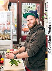 Fast food chef making hotdog in snack bar