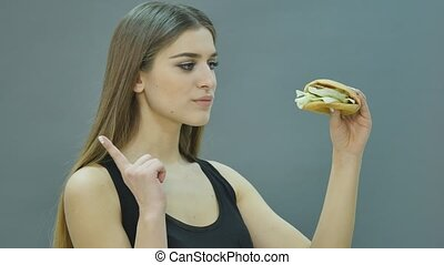 Fast food concept. Tasty unhealthy burger sandwich hamburger in hands hungry mouth getting ready to eat isolated on a black background