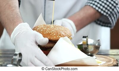 Fast food, hands of chef. French fries and burger.