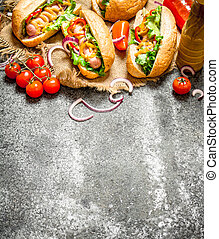 Fast food menu. Hotdogs with onions, peppers, tomatoes and greens dressed with ketchup and mustard.