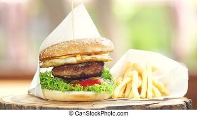 Fast food on wooden board. Burger and fries.