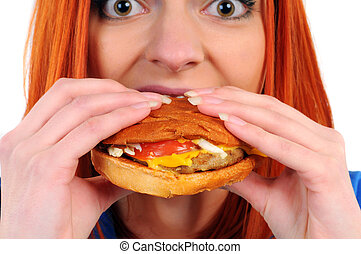 Fast food - Young woman eating hamburger food isolated on a...