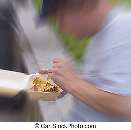 Fast food - Zoom in on man eating fast food (jacket potato)