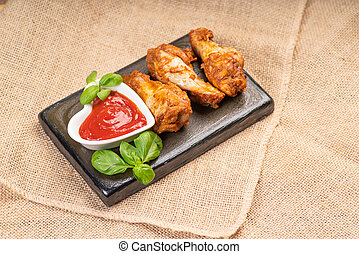 Fast food.Fried chicken wings on a ceramic kitchen board with basil leaves and ketchup