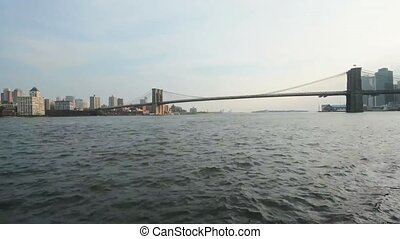 Fast low angle time lapse view on calm ocean water moving in small waves with Brooklyn bridge in background New York