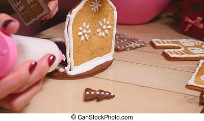 Fast motion of young women build cookie gingerbread house -...
