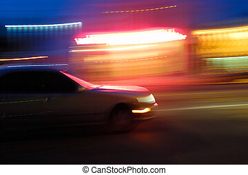 Fast moving car at night, blurred motion.