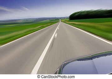 Fast moving car on road - Zooming fast moving car travelling...
