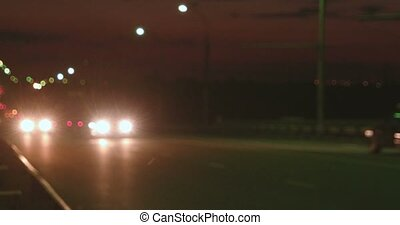 Fast moving cars on overpass in nighttime defocused footage.