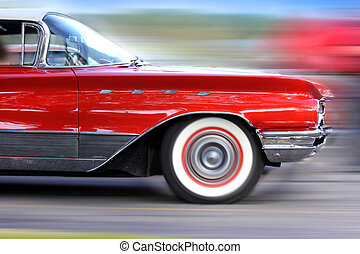 Fast moving classic red car on road