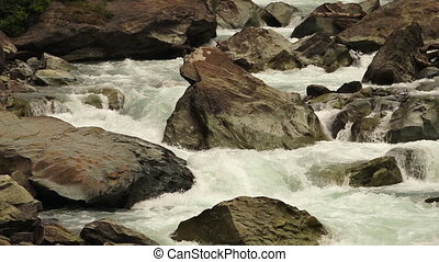 Fast moving river flowing around sharp rocks - Wide shot of...