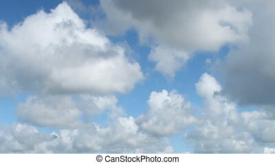 Fast moving white clouds in blue sk