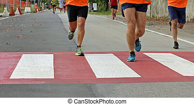 fast runners during a marathon race in the city on a pedestrian crossing