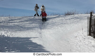 Girl on a sledge pushed down a steep slope bumps into camera