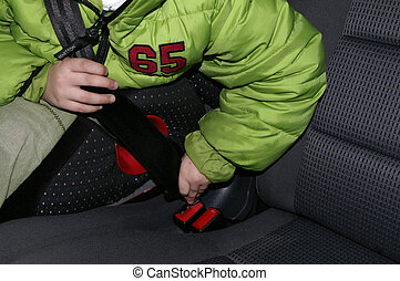 Fasten seatbelt - A child fastens the seatbelt in the car.