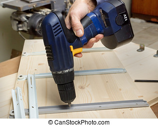 Fastening with an electric screwdriver furniture wooden...