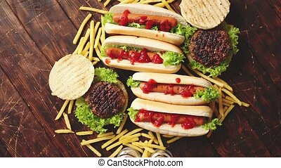 Fastfood assortment. Hamburgers and hot dogs placed on rusty...