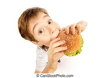 fastfood - Happy nine year old boy eating burger with...