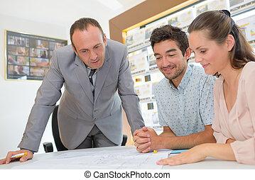 fastighetsmäklare, tittande vid, planer, med, ungt par