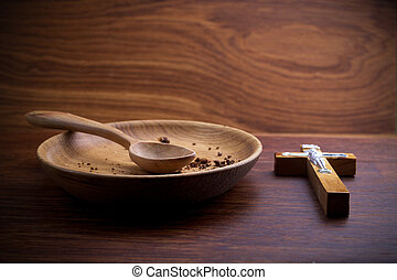 Fasting, Lent. Plate and cross on vintage wooden backgroud.