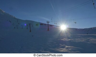 Fastly moving chairlifts on the blue sky background