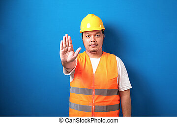 Fat asian workman wearing orange safety vest and yellow helmet making stop gesture