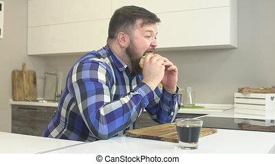 Fat bearded man eats junk food cheeseburger, hurts fast...