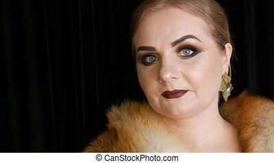 Fat female model with golden makeup and smoky eyes in a coat...