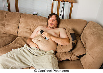 Fat guy sleeping on the couch