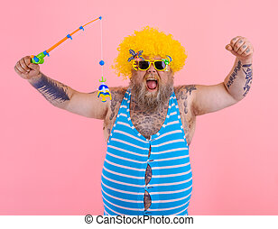 Man with beard and sunglasses have fun with the fishing pole