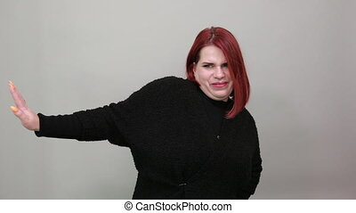 Young redhead fat lady in black sweater on grey background angry woman shows hand stop gesture, doesn't agree