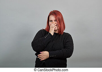 fat lady in black sweater happy woman smiles, covers her mouth with hand, smiles