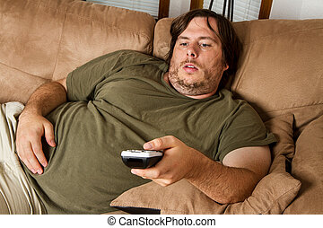 Fat lazy guy on the couch - Overweight guy sitting on the...