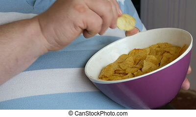 Fat, lazy man is eating potato chips sitting on a chair. A...