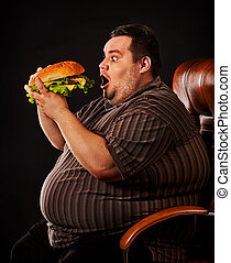 Fat man eating fast food hamberger. Breakfast for overweight person.