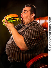 Fat man eating fast food hamberger. Breakfast for overweight...