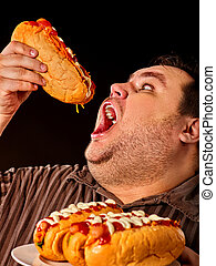 Fat man eating fast food hot dog. Breakfast for overweight person.