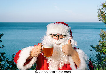 Fat man in glasses dressed as Santa drinking beer on the ocean. Funny, drunk and happy