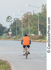 Fat Man Riding a Bicycle on the Country Road.